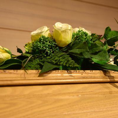 Kukka-asetelma arkun päällä.