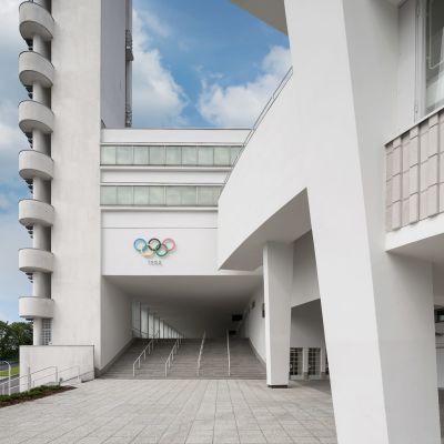 Stadionin tornin viereistä sisäänkäyntiä koristaa edelleen olympiarenkaat.