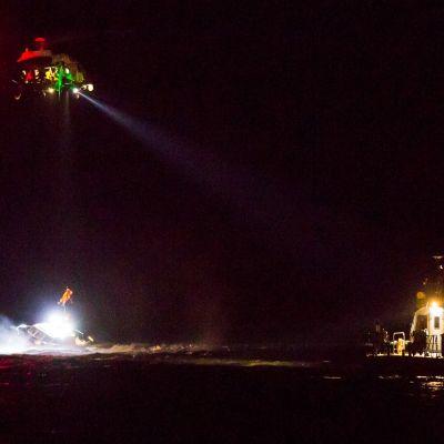 Helikopteri nostaa ihmistä karille ajaneesta veneestä Kotkassa 5.12.2020.
