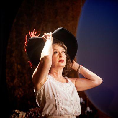 En kvinna i vit klänning med en vid svart musketörshatt på huvudet.