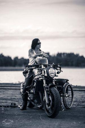 Mustavalkoinen promokuva Tuhkimtotarinoiden Ullasta. Ulla istuu moottoripyörän päällä. Kuvassa näkyy myös Ullan pyörätuoli.