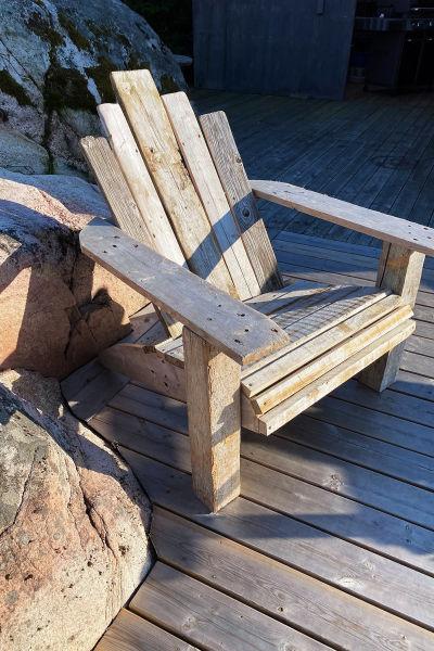 En trästol gjord av plankor står på en brygga.