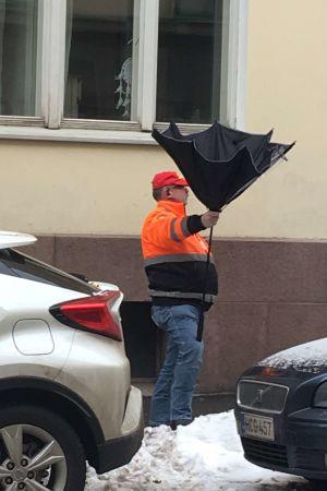 Man fångar karameller i felvänt paraply på penkisdagen.