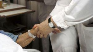 läkare håller patients hand