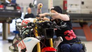 Tuhkimotarinoiden Ulla istuu pyörätuolissa ja samalla ruuvaa kilpamoottoripyöränsä ohjaustankoa.