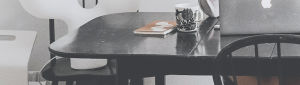 Nainen opiskelee pöydän ja tietokoneen ääressä.