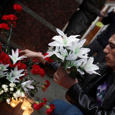 Rysk man placerar blommor efter terrorattacken i S:t Petersburg den 3 april.