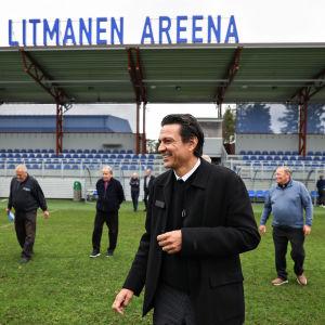 Miehiä vihreällä jalkapallostadionilla.