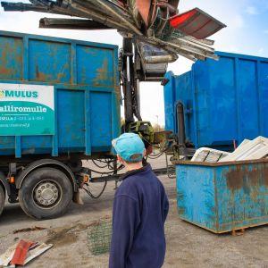 En pojke som står framför en avfallsinsamlingsbil.