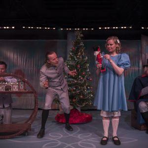 Kolme miestä ja yksi nainen joulukuusen vieressä lahjoja purkamassa.