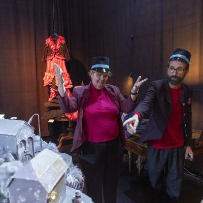 Två personer klädda som museivakter står i ett rum omgivna av scenografi och teaterrekvisita.