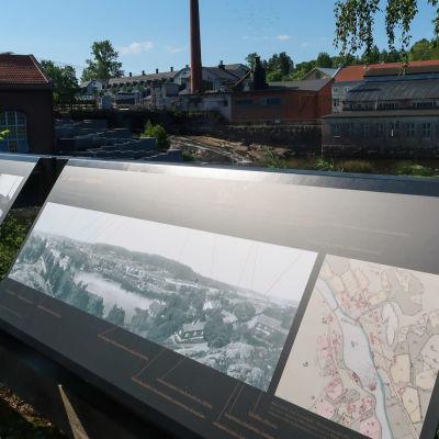 Bild av en skylt med av ett gammalt fotografi av Billnäs. Bakom skylten finns samma vy som på fotografiet.