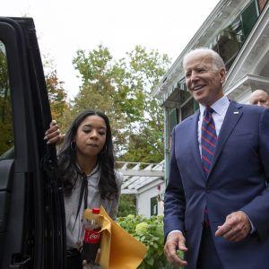 Joe Biden talon edustalla astumassa autoon. Nainen pitää auton ovea hänelle auki.