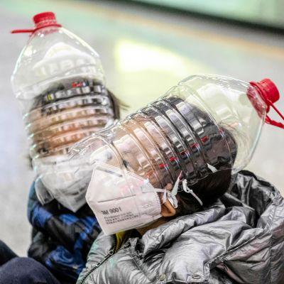 Suojamaskeilla ja muovisilla vesipulloilla peitetyt pikkupojat lastenvaunuissa lentoasemalla.