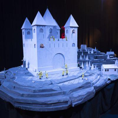 En stort modellandskap av ett slott på en brant och skogig ö.