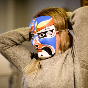 Luciakandidat knyter färgrann mask framför ansiktet.