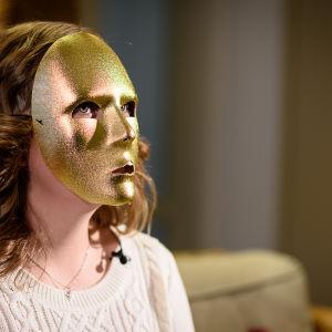 Luciakandidat Cajsa Sundqvist med mask framför ansiktet.