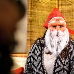 Luciakandidat med julgubbsmask framför ansiktet.