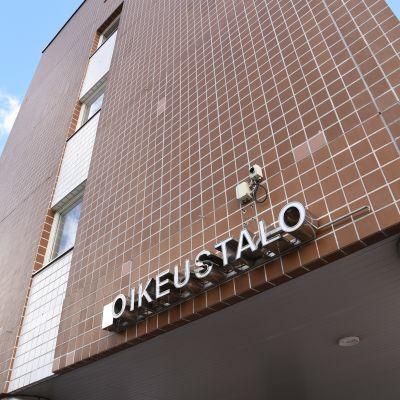 Oulun oikeustalon tiiliseinä ja taustalla kesäinen taivas.