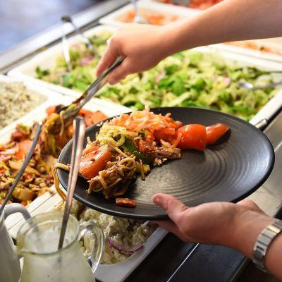 Ruokaa otetaan buffet-linjastolta lautaselle.
