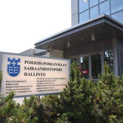 Pohjois-Pohjanmaan sairaanhoitopiiri hallintorakennus, jonka ulko-oven edessä opastekyltti.