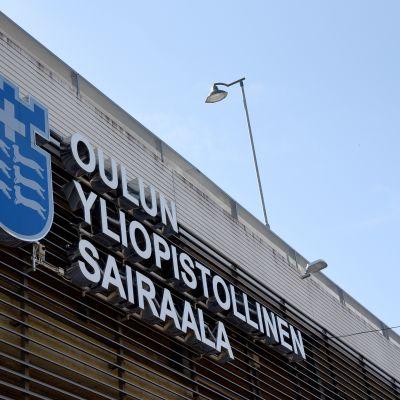 Oulun yliopistollisen sairaalan kyltti sairaalarakennuksen seinässä.