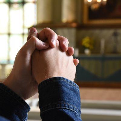 Miehen kädet rukousasennossa kirkon alttarin edessä.