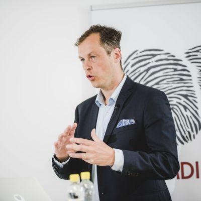 Janne Artikainen fotad med gestikulerande händer