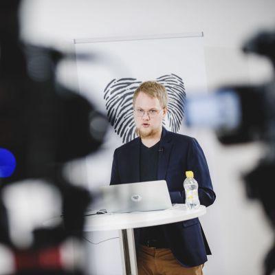 Rasmus Aro fotad på presskonferens när han talar vid podium