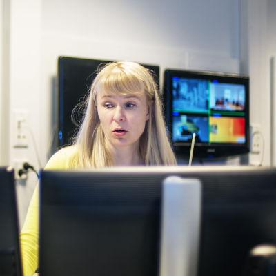 toimittaja katselee kuvia useilta rinnakkaisilta monitoreilta. Taustalla näkyy isoja ruutuja, joissa on kuvia verkkouutisista ja uutislähetyksistä