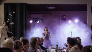 Kukka-yhtye esiintyy Varkauden klubilla dekkarifestivaalin iltatapahtumassa, ihmisiä pöytien ääressä.