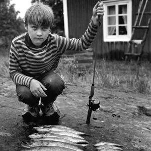 Tomi Salmela lapsena Kemiössä kalansaaliin kanssa.