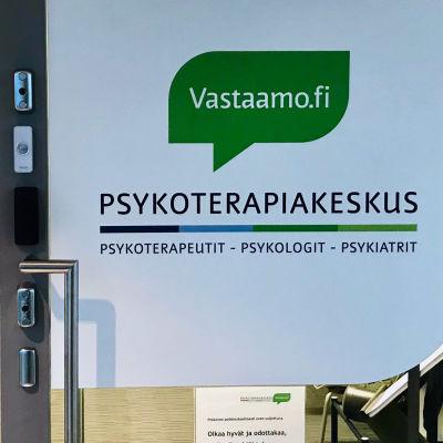 Glasvägg och glasdörr in i ett väntrum. På dörren finns texten Vastaamo Psykoterapiakeskus.