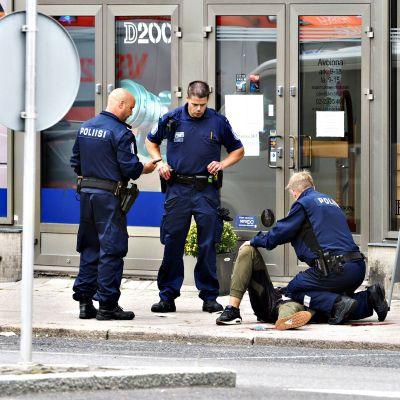 Kuva Turun puukottajasta 18. elokuuta 2017. Poliisit ovat ympäröineet maassa makaavan miehen.