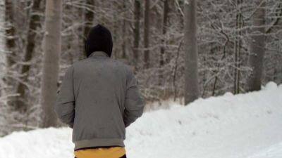 30-åriga Ali på en snöig skogsväg i Finland. Han står med ryggen vänd mot kameran och en huva på huvudet.