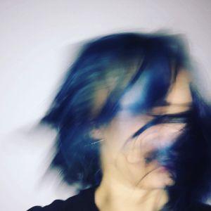 Emma Raunios promofoto med håret som blåser framför ansiktet och döljer det.