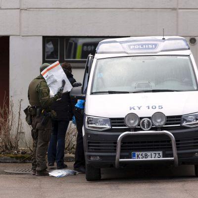 Bild på Polisbil utanför hus i betong. Brevid bilen står polis och man klädd i jeans.