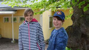 Två barn står framför en gul byggnad och tittar in i kameran.