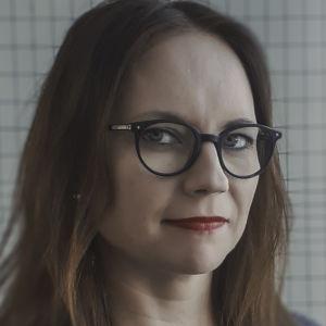Redaktör Eva Pursiainen, kvinna med långt brunt hår, blå ögon och glasögon.