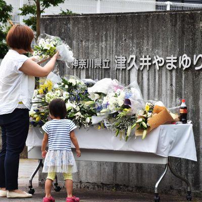 Äiti ja tytär tuovat kukkia puukotuksen uhreille Japanilla heinäkuussa 2016.