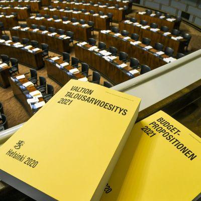 Vuoden 2021 budjettikirja kuvattuna eduskunnan istuntosalissa.