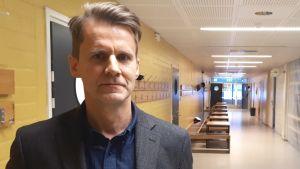 Man med blå skjorta och grå kavaj står i en tom skolkorridor.