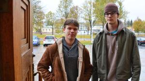 Två unga män står i en dörröppning. Bakom dem syns Lovisa gymansiums gårdsplan.