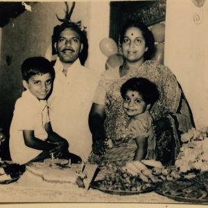 Srilankalainen 4-henkinen perhe 80-luvulla otetussa kuvassa. Pienet poika ja tyttö istuvat pöydällä ruoka- ja hedelmätarjotinten keskellä, vanhemmat seisovat lasten ja pöydän takana.