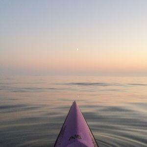 Kuvan alalaidassa kanootin nokka, joka suuntaa kohti avovettä ja taivaanrantaa.