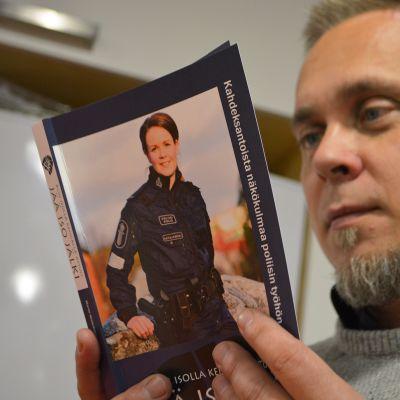 Poliisiviestinnän lehtori Marko Vesterbacka pitelee poliisiammattikorkeakoulun pääsykoekirjaa.
