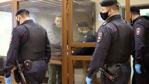 Aleksej Navalnyj iklädd en grå jacka förs in i en glasbur av flera polismän.