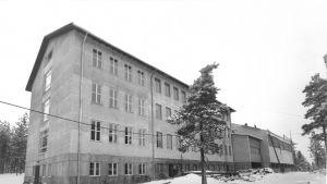 En svartvit bild på när Virkby samskola byggs ut.