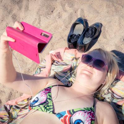 Kvinna på stranden. Hon ligger och tittar på video via sin mobiltelefon.