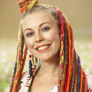 Vegas sommarpratare 2019 Vicky O'Neon. Hon har långa garndreads i glada färger. Hon står framför en sommaräng.